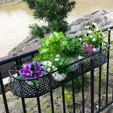 wrought iron railing fence flower pots hanging oval frame balcony