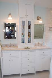 white bathroom wall cabinet with towel bar and glass doors using