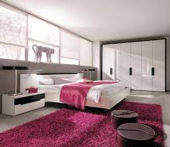 modern pink bedroom pink black lines pattern painted wall parquet and study table rug white green bed cabinet