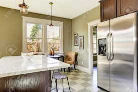 olive tone kitchen room with steel refrigerator and marble top