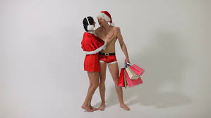 funny christmas couple in red santa claus hats of handsome man