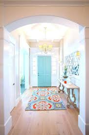foyer entry with colorful runner and an aqua painted front