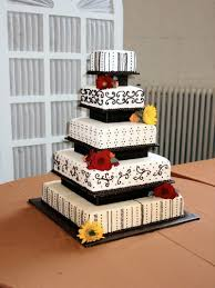 cake place 5 tier white wedding cake with black scrolls and red