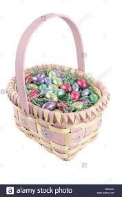 a pretty easter basket filled with chocolate candy eggs isolated