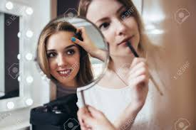 looking for makeup artist client looking in the mirror while makeup artist
