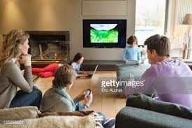 Family Using Electronic Gadgets In A Living Room Stock Photo - Family in living room
