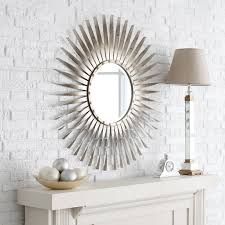 decorating gold sunburst mirror with beige wall and console table