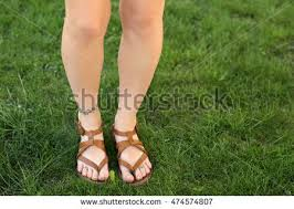 female legs tattoos on green grass stock photo 474574846