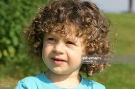cute little boy with curly hair outdoors stock photo getty images