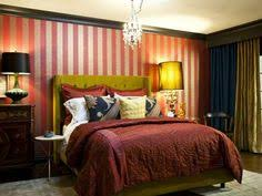 dark red paint color in this master bedroom with gold curtains
