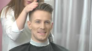 usinghair cls barber using hair spray handsome caucasian man with undercut