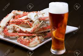 plate with a pile of crab legs and a glass of amber beer clipping