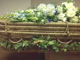 seagrass coffin with natural garden flowers posies spray and