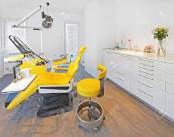 yellow dental chair and stool in dentist office stock photo