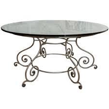 round glass top dining table with attractive wrought iron base