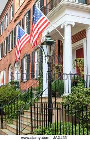 old brick home with american flag hanging on front porch stock