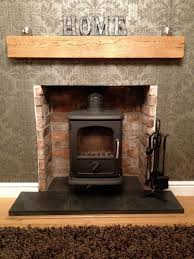 brick stone fireplace with black metal fire box and brown wooden