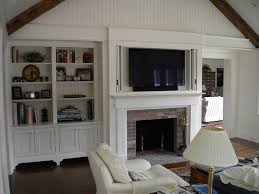 television cabinet above fireplace mantle with accordion style pocket doors flanked by custom bookcases with bracketed