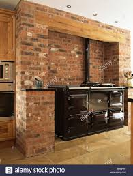 black double aga oven in exposed brick wall in country kitchen