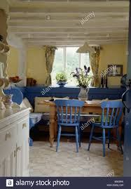 painted blue chairs and settles in yellow cottage kitchen dining
