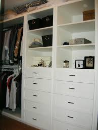 elegant white wooden closet shelving unit with storage drawers of