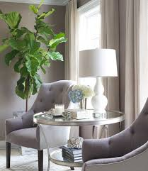 round silver accent table sitting room boasts a pair of gray tufted chairs flanking a round