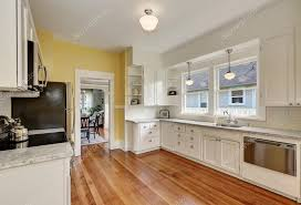 white kitchen cabinets wood floors kitchen interior with white cabinets yellow walls and wood floor 121788116