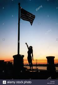 American Flag Sunset Silhouette Of Woman In Sunset Standing Next To American Flag Stock