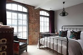 elegant bedroom with the brick wall material feat dark brown iron