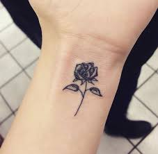 small black rose tattoo on wrist