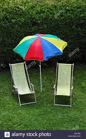 Two Beach Chairs Idyllic Garden Scene Two Beach Chairs And A Parasol In A Garden