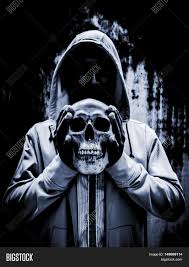 background for halloween release your evil person holding human skull in hand scary