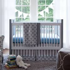 interior grey and blue crib bedding on white and grey wooden crib