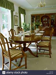 oval mahogany table and upholstered chippendale style chairs in