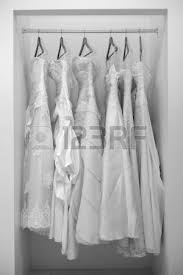 white wedding dresses hanging on shoulders and pegs stock photo