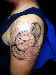 picture of clock with two roses tattoo on the shoulder