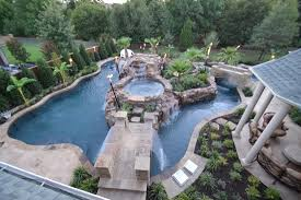 top view large backyard lazy river pool design with small pool in the middle with waterfall plus stone floor tiles and surrounded by garden ideas