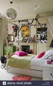 single four poster bed with fairy lights in teenage u0027s bedroom