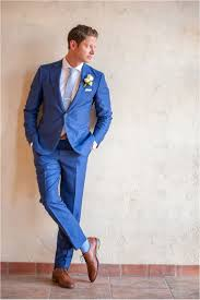 dapper groom in royal blue suit with saddle color shoes and pale