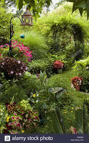 backyard garden path with arbor ornaments bird feeder coleus