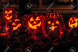 group of candle lit carved halloween pumpkins sitting on fallen