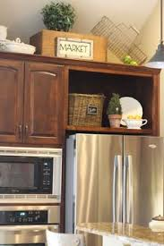 space between top of refrigerator and cabinet she took the cabinet doors off above the fridge for extra decor