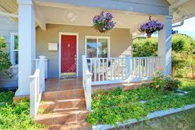 House Porch by Grey House Porch With Red Door And White Railings Stock Photo