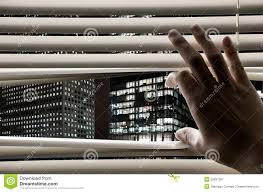 man opening window blinds seeing business towers royalty free