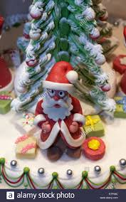 santa claus figure made of marzipan decoration on a cake in the