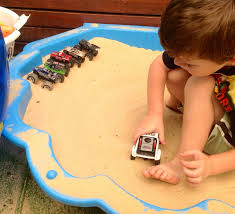 boy playing sand sandpit toy monster truck race racing