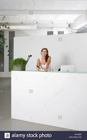 Free Reception Desk A Woman Behind An Office Reception Desk With A Notepad And Pen