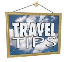 travel tips words on a hanging sign with clouds in blue sky
