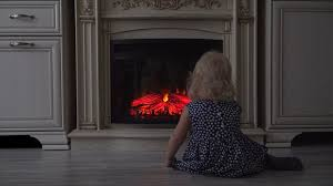 little looks at artificial fire in the fireplace stock video