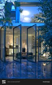 rear elevation of a renovated modern house with an open glass wall